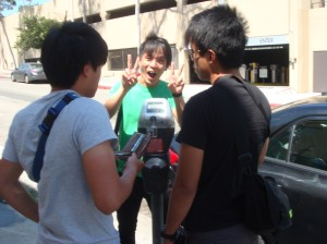 Normen gives the victory sign, as Cheng Yew and Jastine figure out the parking meter.